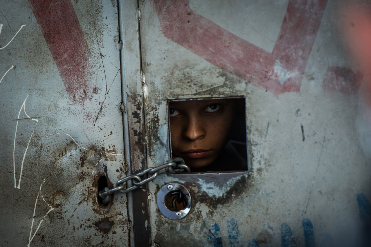 February 9, 2012. A resident looks outside from a peephole at the entrance of an ilegally occupied building before being evicted in downtown Sao Paulo.