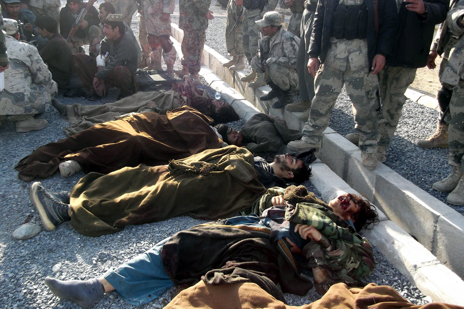 Feb. 28, 2012. Afghan army soldiers stand besides the bodies of alleged Taliban militants after a gun battle between Taliban and Afghan police after an attack at Afghan police station in Jalalabad province, Afghanistan.