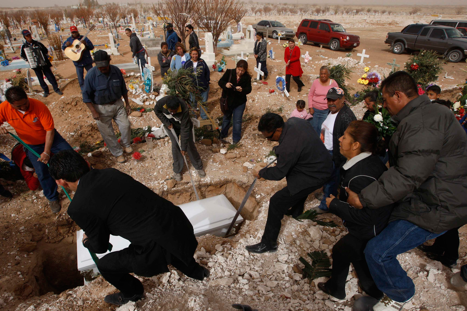 Feb. 28, 2012. Friends and family members mourn as the coffin of Garcia Pena is lowered into the ground at a cemetery on the outskirts of Ciudad Juarez, Mexico.