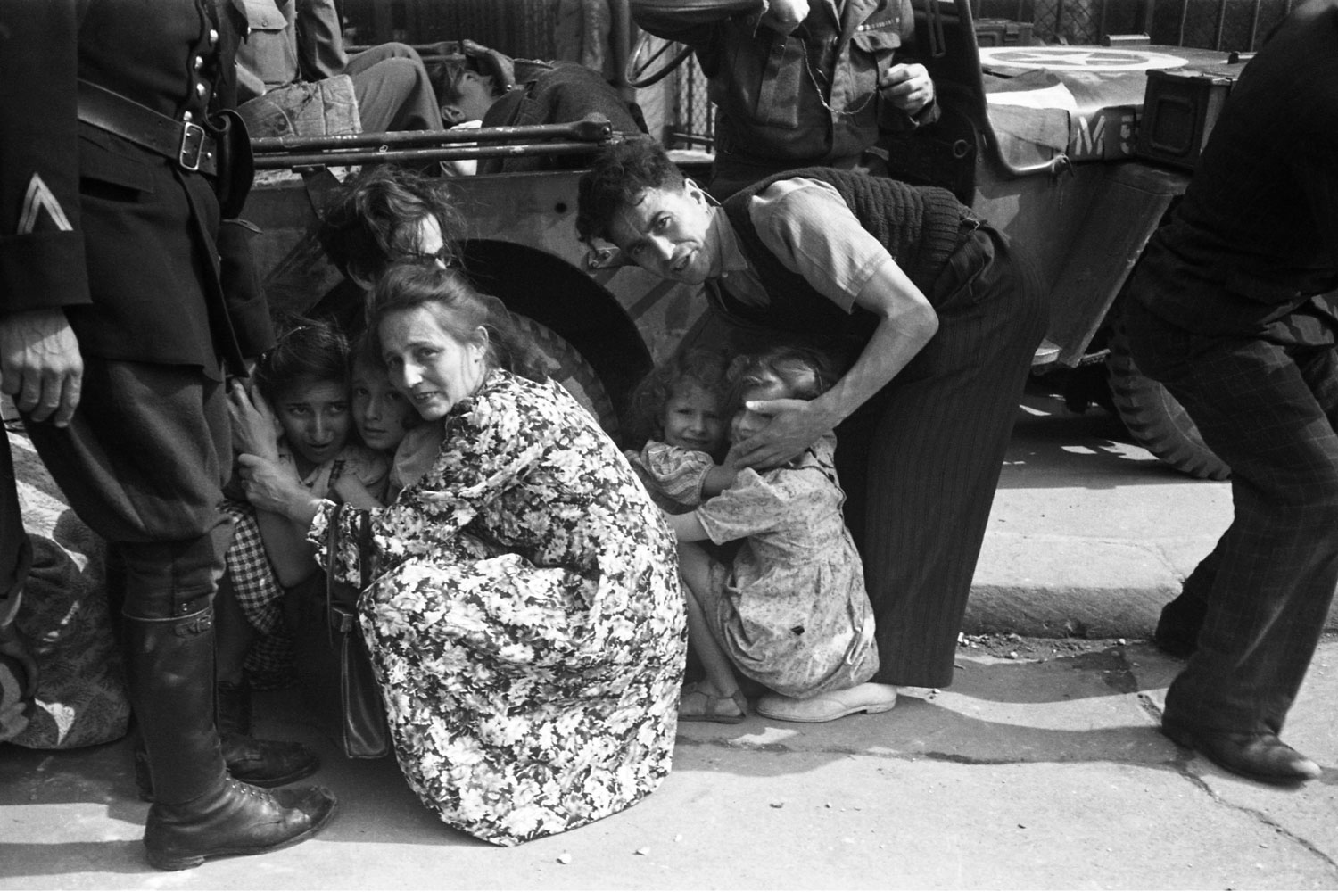 A family seeks safety beside a Jeep as French Resistance fighters and Free French troops try to take out a German sniper during the Liberation of Paris in August 1944.