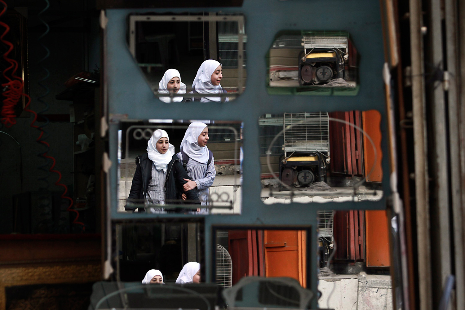 Feb. 25, 2012. Palestinian girls are reflected in mirrors displayed for sale outside a shop in Jabaliya town, North Gaza Strip.