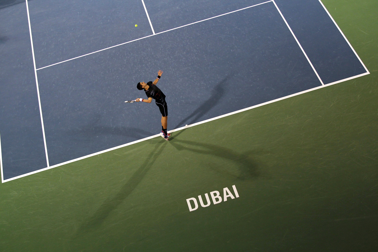 Feb. 27, 2012. World number-one tennis player Novak Djokovic of Serbia serves to Cedrik-Marcel Stebe of Germany during their ATP Dubai Open tennis match in the Gulf Emirate.