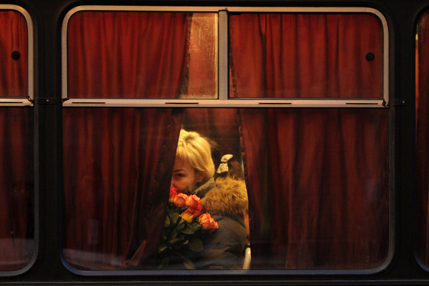 Feb. 28, 2012. An activist of the opposition holds flowers as she sits in a police bus after a rally in front of the Russian Central Election Commission headquarters in Moscow after their attempt to hold an unauthorized protest against the upcoming March presidential poll.