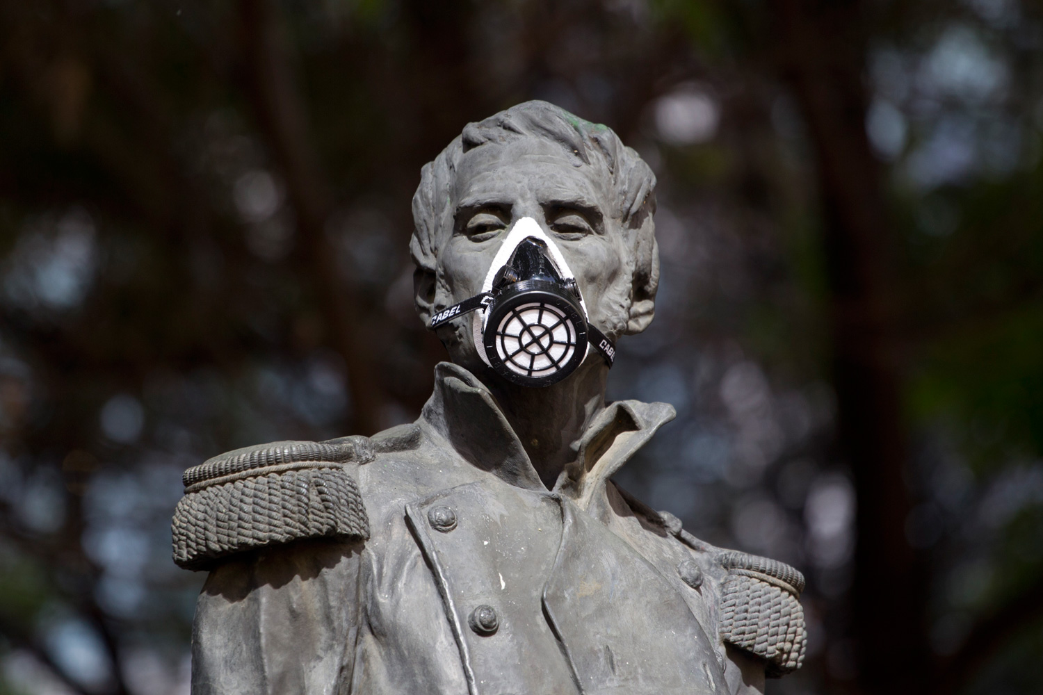 Feb. 28, 2012. A gas mask covers the mouth on the statue of independence hero Leonardo Bravo to protest pollution in Mexico City.