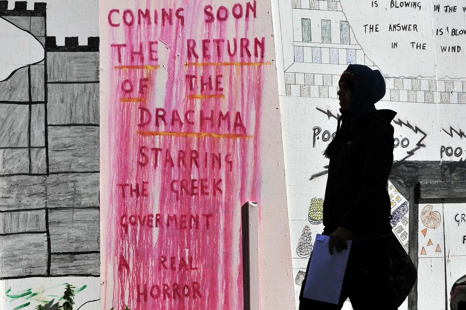 Feb. 28, 2012. A person is seen silhouetted against protest slogans on a wall in the center of Athens.