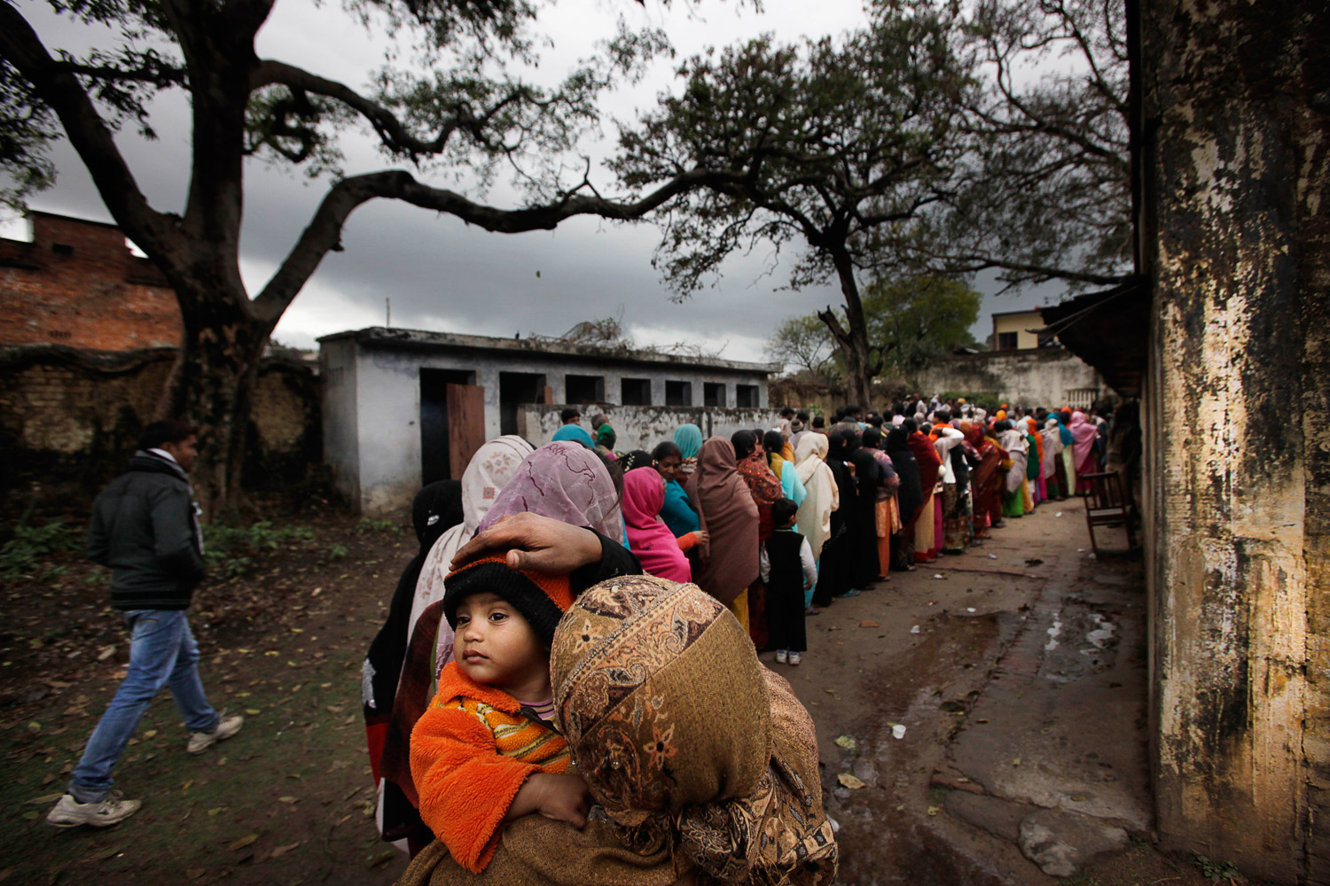 February 8, 2012. An Indian woman adjusts the cap of her child as she waits in a queue to cast her vote, in Ayodhya, India.