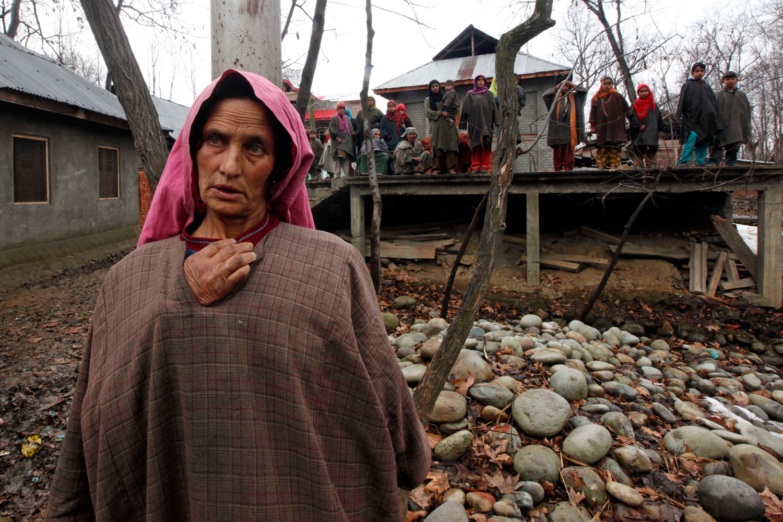 February 4, 2012. A Kashmiri village woman stands near the site of a gunbattle in Woodder village, south of Srinagar, India.