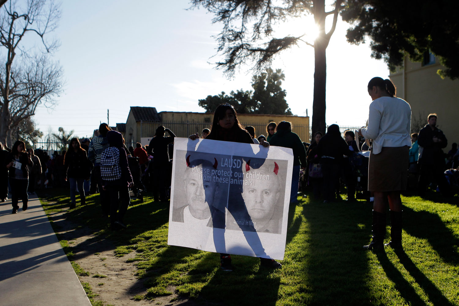 February 9, 2012. Ashley Villatoro, 9, holds a sign showing images of former teacher Martin B. Springer outside Miramonte Elementary School in Los Angeles. The entire staff of the school has been replaced following the arrests of two former teachers on charges of committing lewd acts with students.