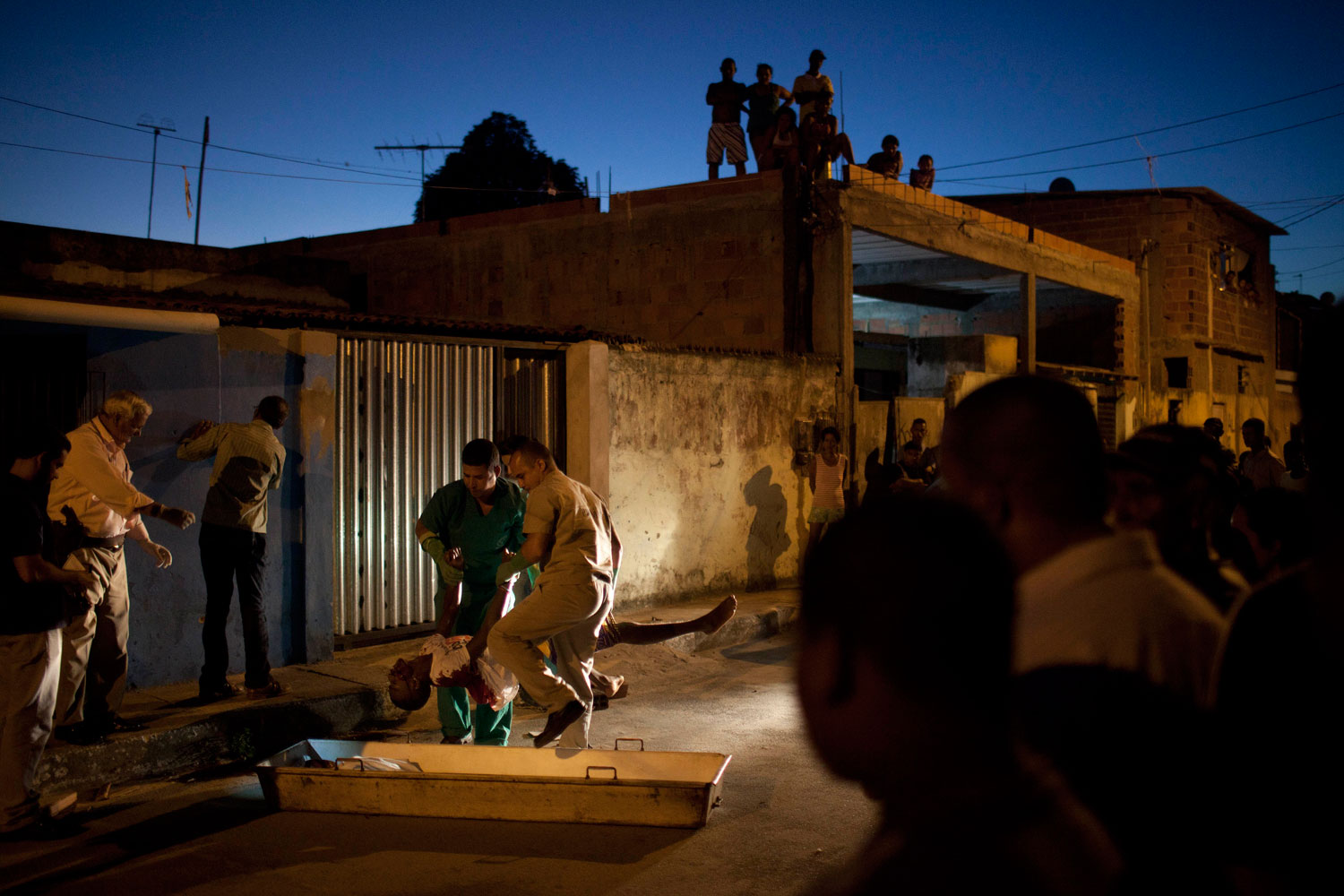 February  8, 2012. Morgue workers remove the body of a man killed during a shooting from the crime scene at Itinga neighborhood in Salvador, Brazil. About one-third of Bahia state's 30,000 patrolling police went on strike last week. During the strike the murder rate in Salvador, the nation's third-largest city, doubled.
