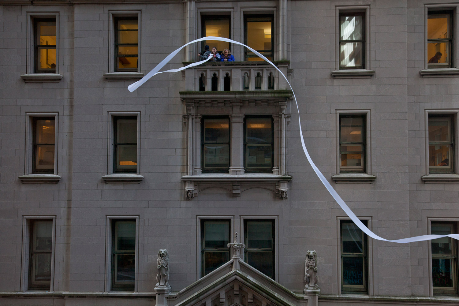 February 7, 2012. Spectators gather on a balcony to watch the New York Giants victory parade in New York. The Giants returned from their Super Bowl win to a ticker-tape parade in the Canyon of Heroes on Broadway.
