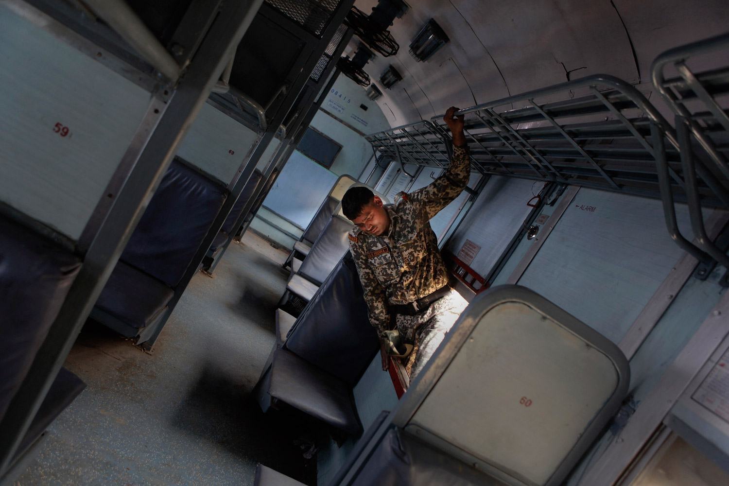 February 3, 2012. An Indian disaster response worker searches a rail car for casualties in a derailed passenger train following an accident at Sathi Sarapa village near Gauhati, India.