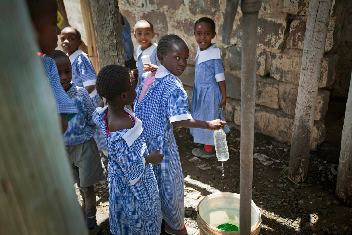 February 2, 2012. Schoolgirls fill a bottle of water from a tank supplied by a borehole at their school in the Karagita slum next to Lake Naivasha, during a visit by Rachel Kyte, Vice President of Sustainable Development for the World Bank, unseen, in Kenya.