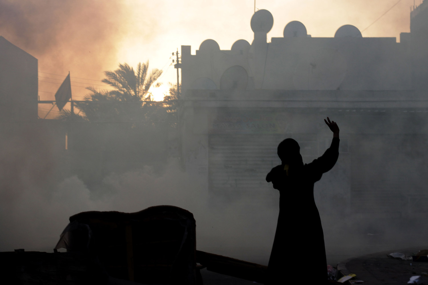 February 6, 2012. A Bahraini woman shouts anti-government slogans as she gestures toward riot police firing tear gas in the western village of Malkiya, Bahrain.