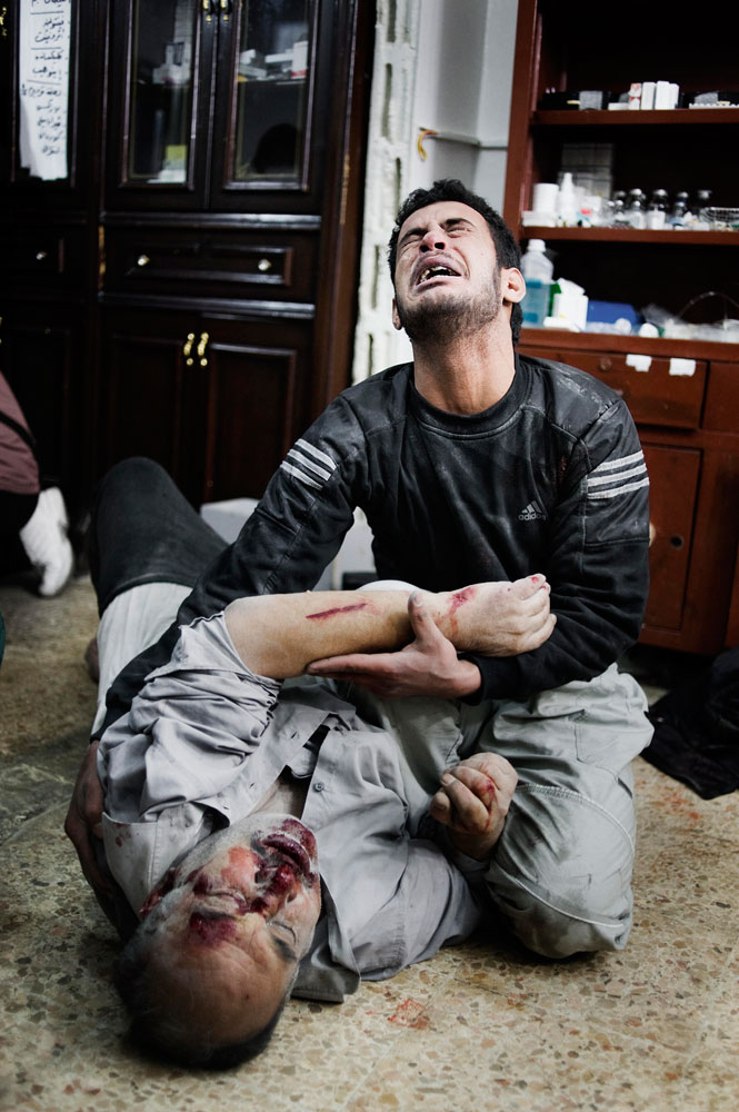 A Syrian man holds his wounded brother in a house that is used as a hospital in Bab Amr, a southern neighborhood of Homs. Feb. 6, 2012