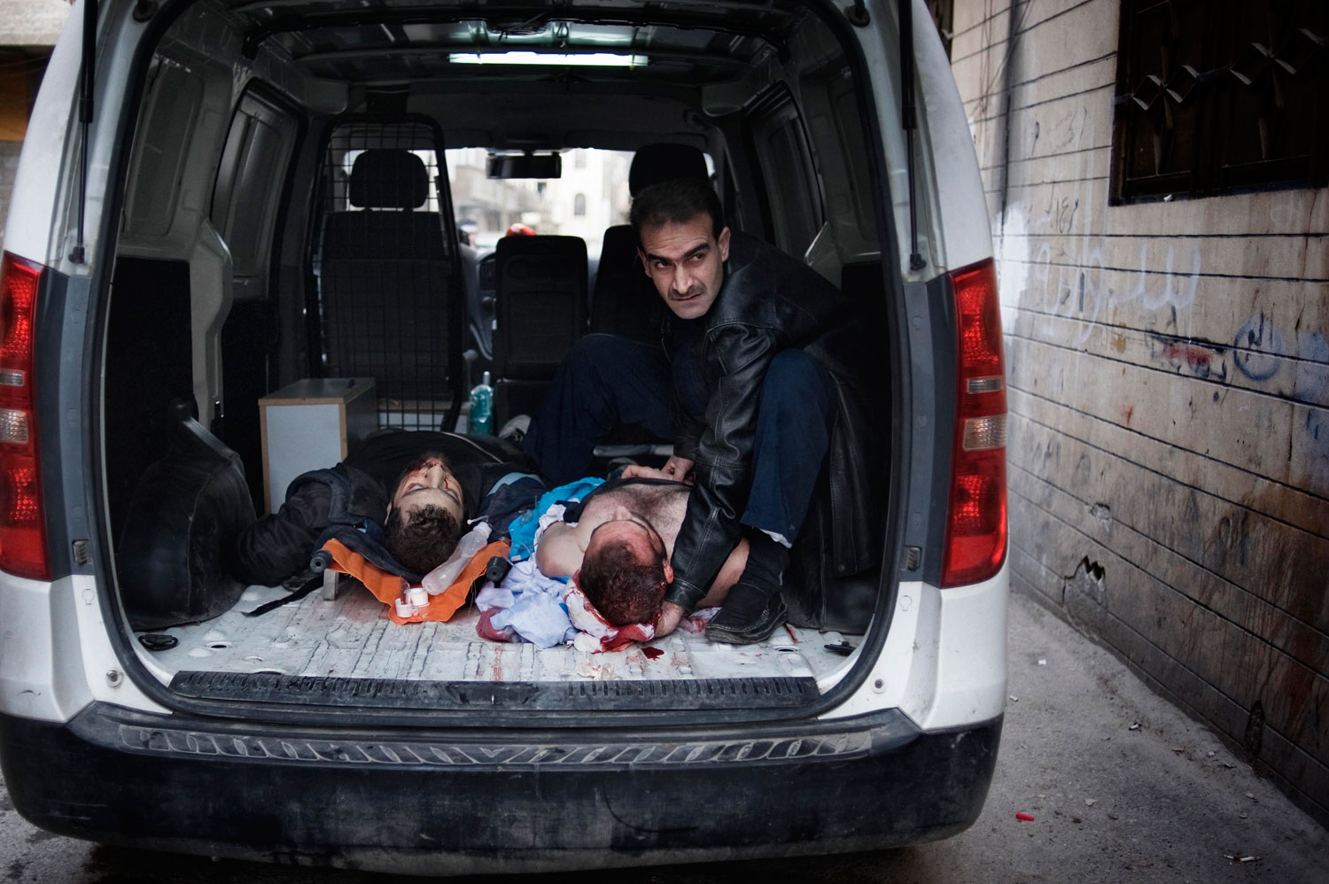 A Syrian man holds the head of a severely wounded man at the entrance of a house that is used as a hospital in Bab Amr. Feb. 6, 2012