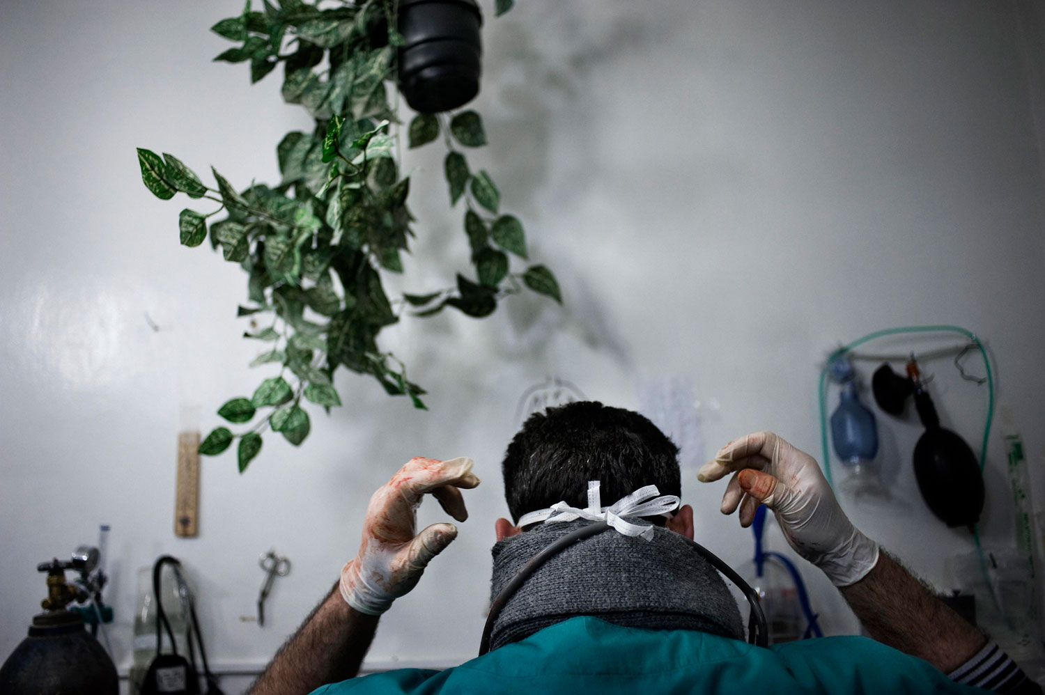 A Syrian doctor prepares to perform surgery on wounded men in a house that is used as hospital in Bab Amr. Feb. 6, 2012