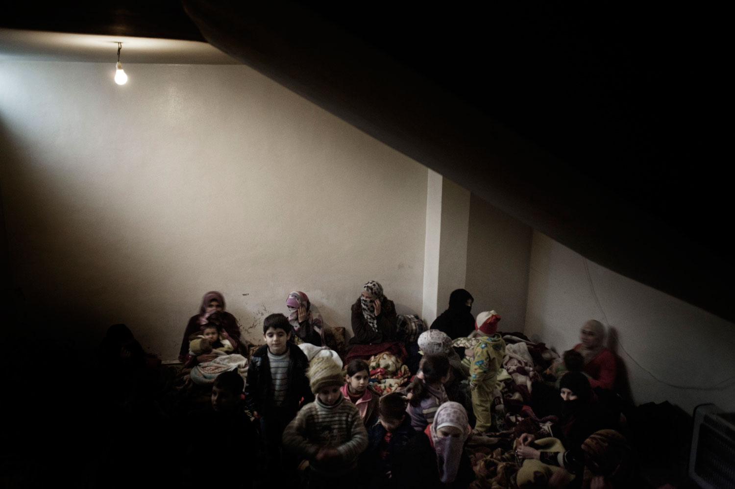 Displaced women and children seek shelter from shelling in a basement in Bab Amr. Feb. 7, 2012