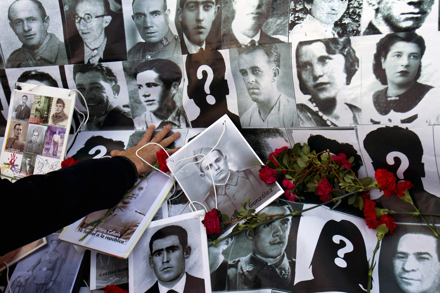 February 8, 2012. A demonstrator touches a banner showing photos of some Spanish Civil War victims during a protest outside the Supreme Court on the last day of judge Baltasar Garzon's trial in Madrid.