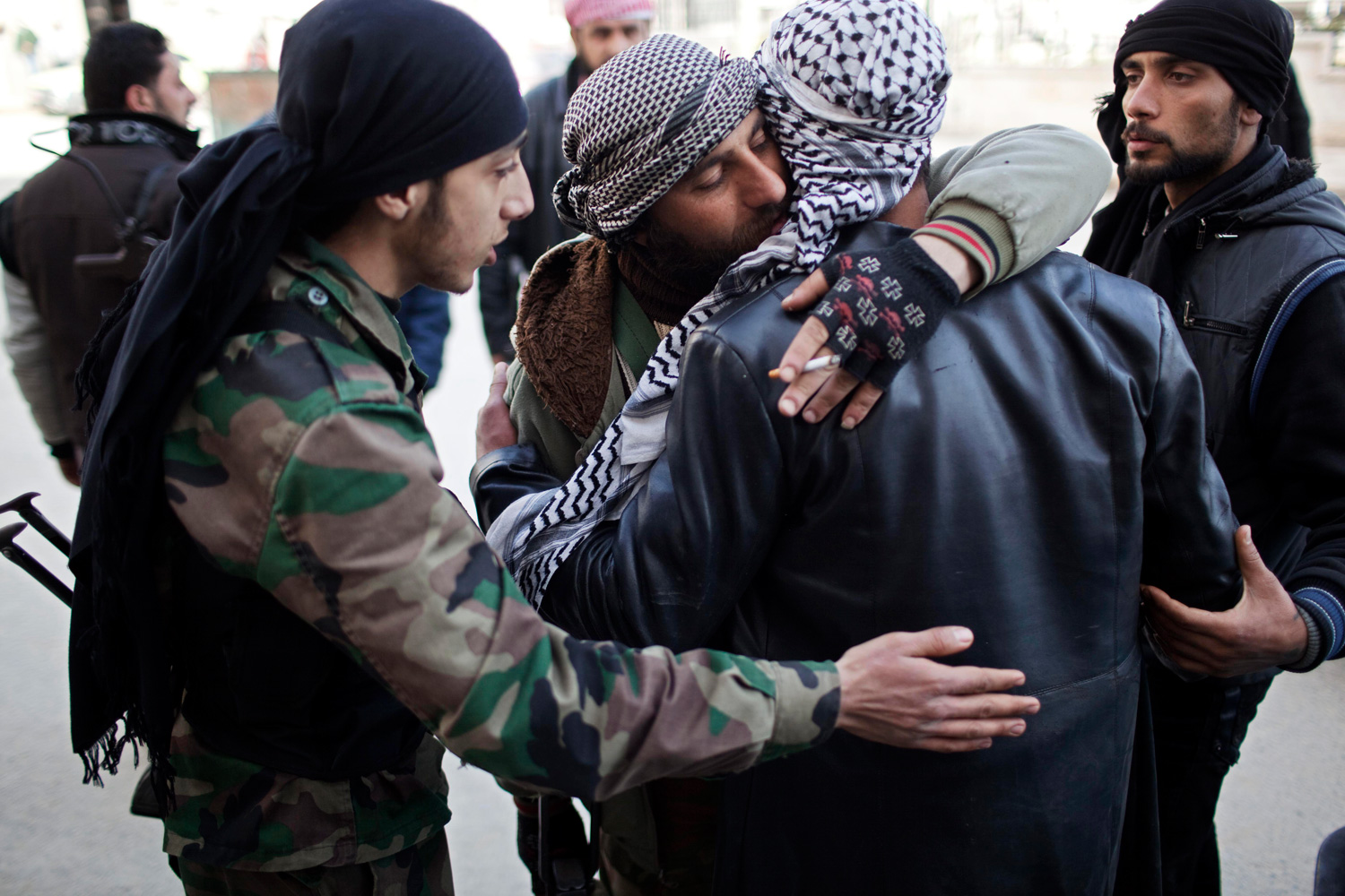 March 10, 2012. Free Syrian Army fighters console a comrade after an ambulance carried an injured friend to a hospital during fierce fighting against government troops in Idlib, north Syria.