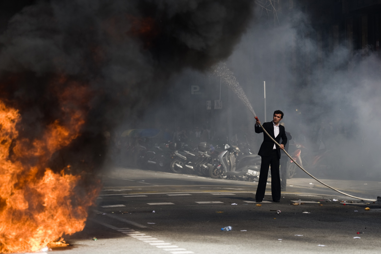 Feb. 29, 2012. A hotel receptionist tries to put out a fire during a demonstration in Barcelona.