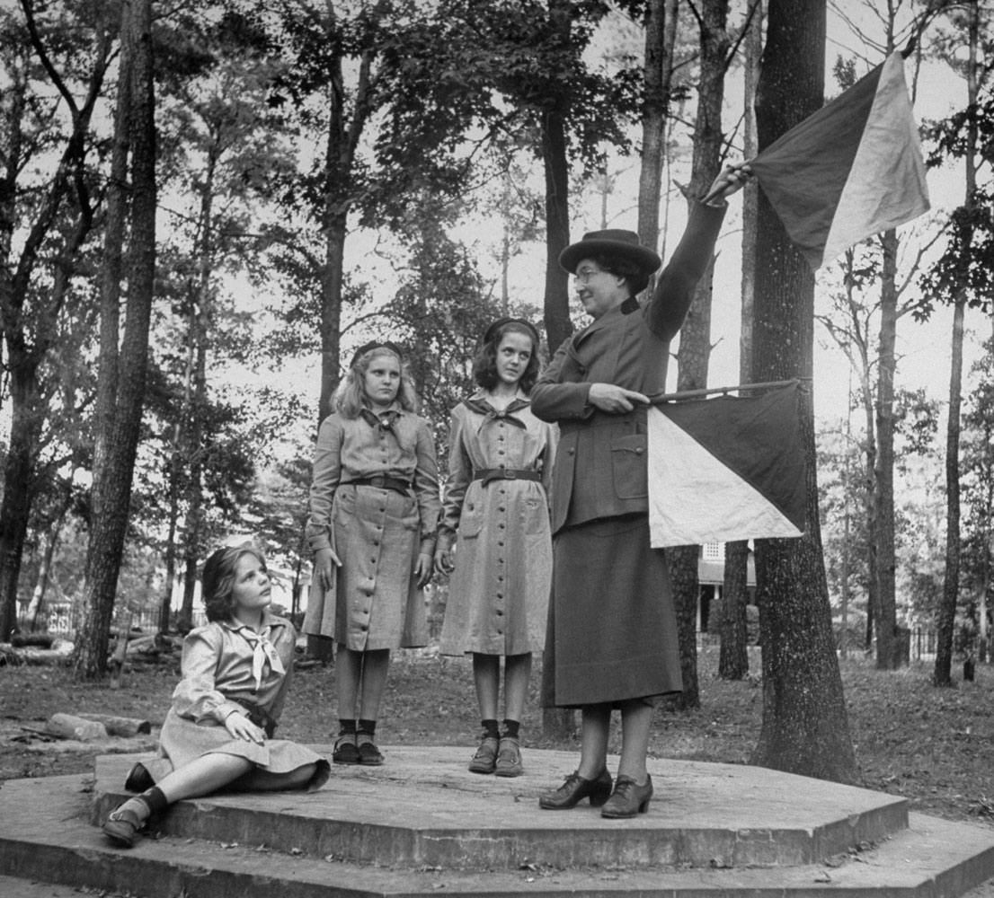 <b>Caption from LIFE.</b> Signaling, Mrs. Lawrence waves semaphore flags. She can remember most letters up to M, also W (above). She has three children; all were boy scouts.