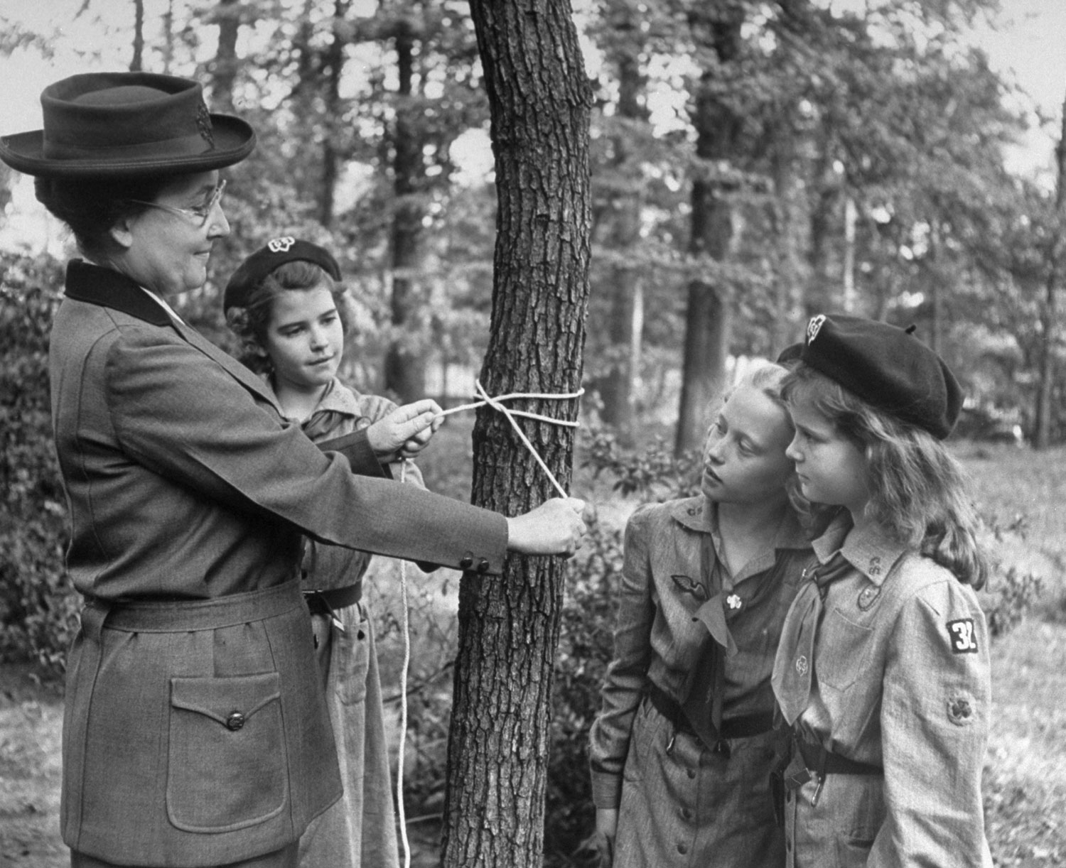 <b>Caption from LIFE.</b> Tying knot, she makes clove hitch on a tree. Modern scouts do less knotting and woodcraft, concentrate more on homemaking and hospital work.