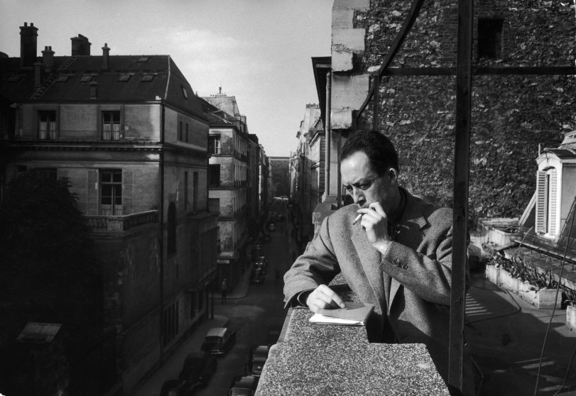 French writer Albert Camus smokes a cigarette on the balcony outside his friend and publisher Michel Gallimard's office in Paris, 1955. Camus won the Nobel in 1957; in 1960, when he was 46 years old, he was killed in a car crash along with Gallimard, who was driving.