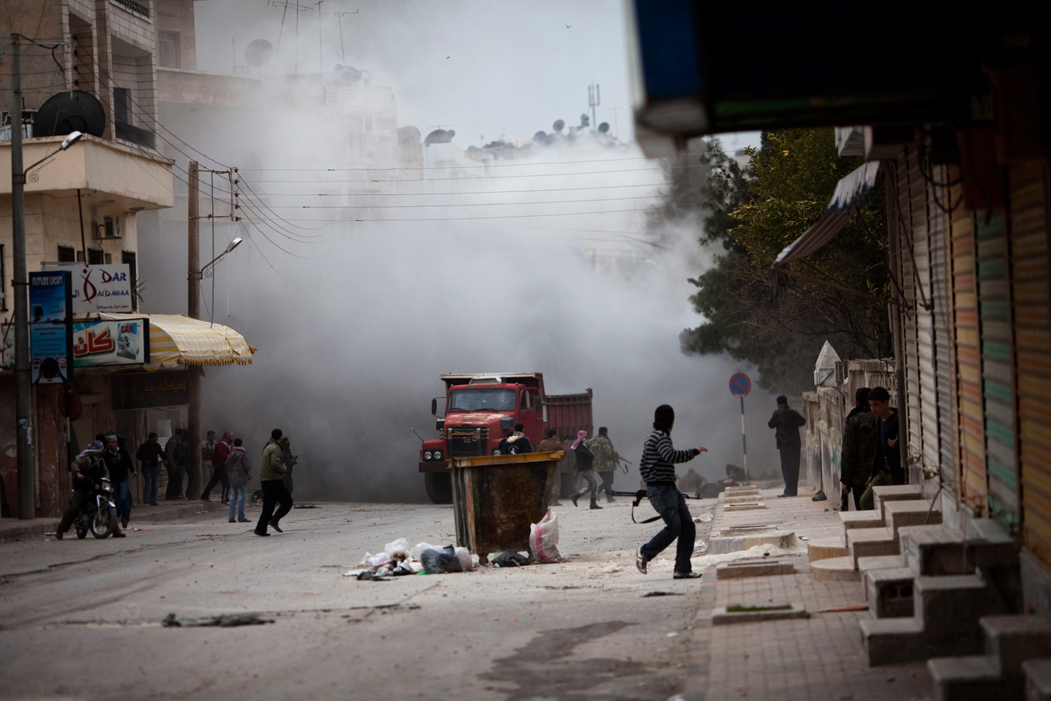 March 11, 2012. Free Syrian Army fighters are seen amid smoke from tank shelling during a day of fierce fighting with the government forces in Idlib, north Syria.