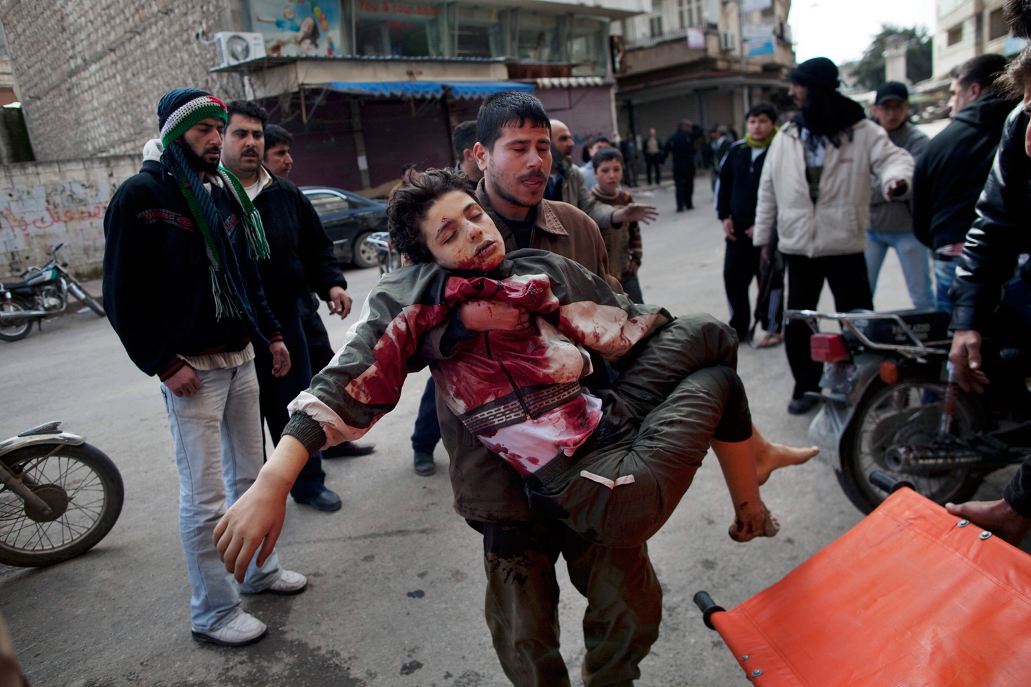 March 11, 2012. A man carries a boy who was severely wounded during heavy fighting between Syrian rebels and government forces in Idlib, north Syria.
