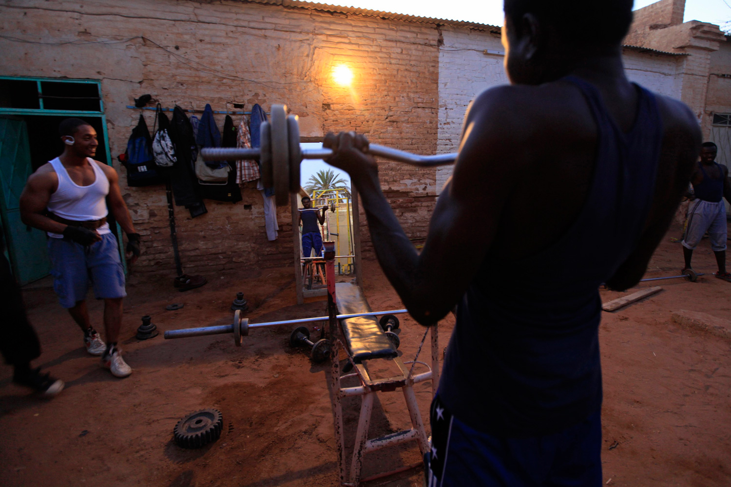 Feb. 28, 2012. A member of the national weightlifting team lifts weights as he prepares to compete with other athletes for the selection of the Olympics team in Khartoum, Sudan.