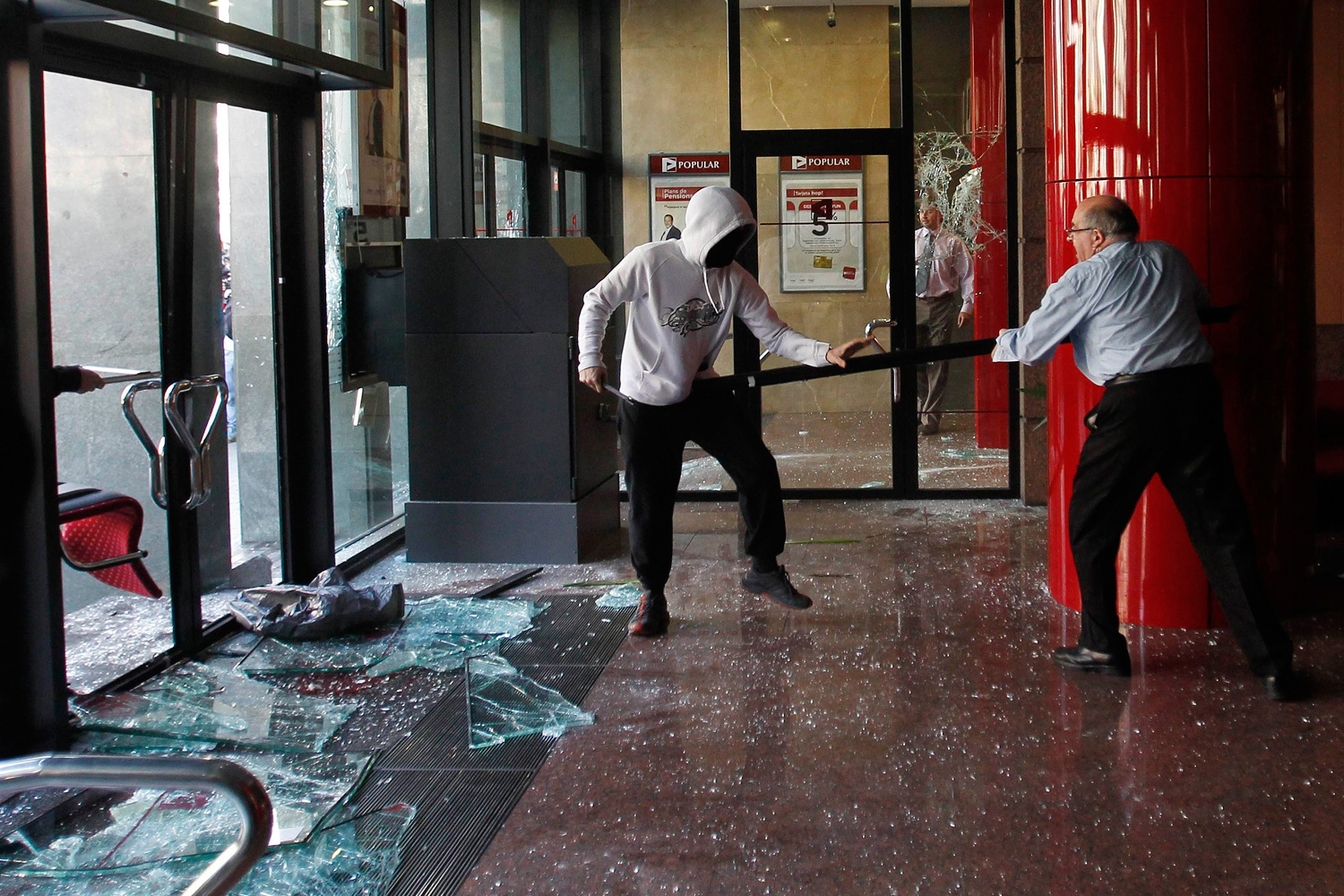 Feb. 29, 2012. A man confronts a hooded protester who was vandalising a bank during a protest against cuts in public education in Barcelona .