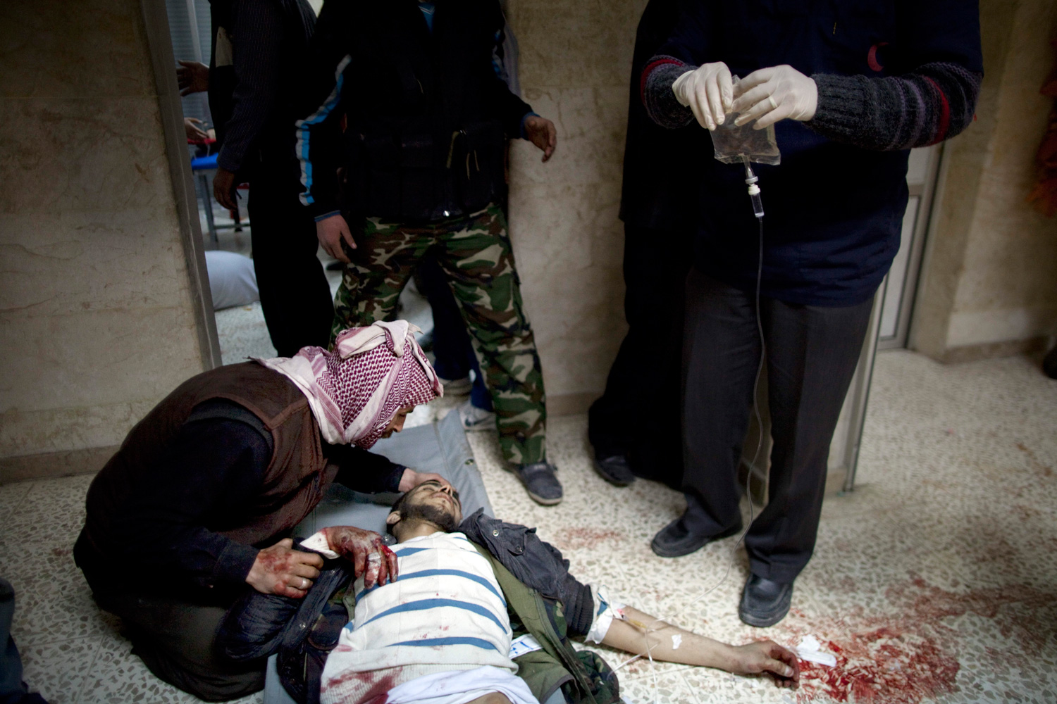 March 11, 2012.  A man tries to help a Syrian rebel after being wounded by fragments of an exploding shell in Idlib, north Syria.