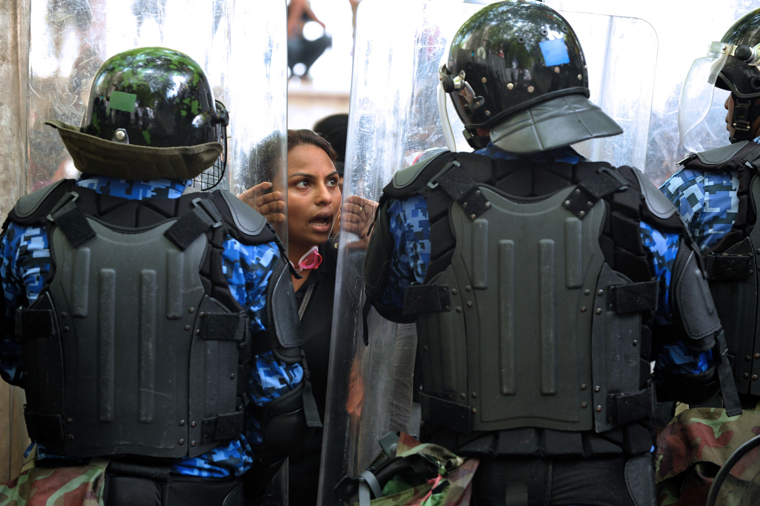March 1, 2012. Maldivian policemen stand guard as a protestor shouts slogans during a rally in Male.
