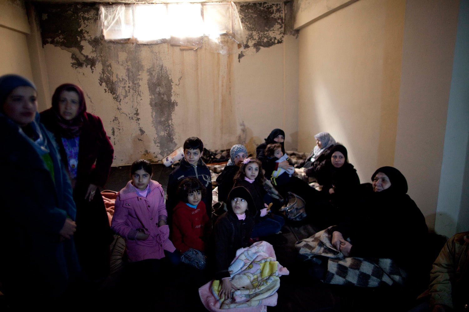 March 10, 2012. Syrian women and children take shelter from fierce fighting between the Free Syrian Army and government troops in Idlib, north Syria.