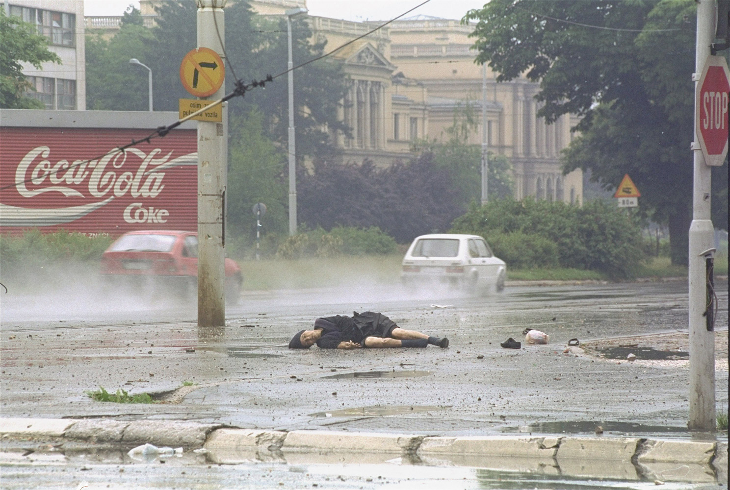 June 11, 1992. Sarajevo. On Thursday, June 11, 1992, I was in an a 'soft' (non-armored) car speeding out of central Sarajevo on the infamous 'Sniper Alley' when, out of the corner of my eye, I saw a body in the street. The dead woman had been walking towards Sarajevo, presumably from the countryside, given her attire, and had passed along a stretch of road exposed to Bosnian Serb or Serb snipers. Someone had shot her in the head and her body lay exposed on the road as cars sped by at top speed to avoid a similar fate.I approached the body, crouched down low behind a metal garbage container in order to make a photo, always aware that I might be visible to another sniper. At some point I stopped, framed the photo with an 80-200 f2.8 zoom lens and waited for something to fill the background. A car sped by. I lowered my shutter speed slightly to try and capture the movement of what I assumed would be another car passing by soon. One did and I released the shutter.At this stage very, very few journalist were working in Sarajevo due to the dangerous conditions and difficulty of accessing the city. There was much interest in the rapidly deteriorating situation there. The photo was used on scores of newspaper front pages around the world. Some years later I was sent a photo taken at a photo exhibition in Sarajevo. One whole wall of the exhibition consisted of front pages featuring this photo.