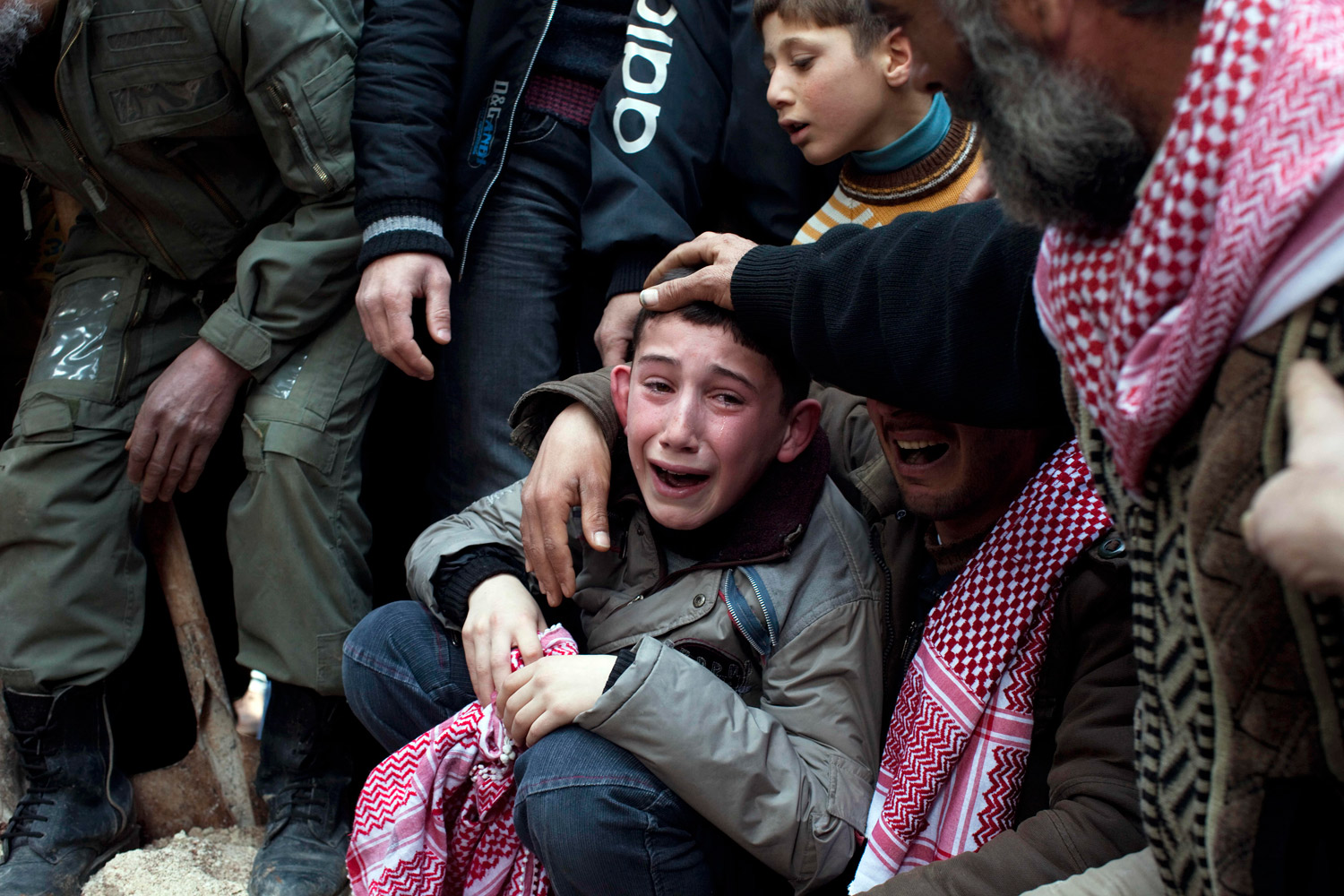 March 8, 2012. Ahmed, center, mourns his father Abdulaziz Abu Ahmed Khrer, who was killed by a Syrian Army sniper, during his funeral in Idlib, north Syria.