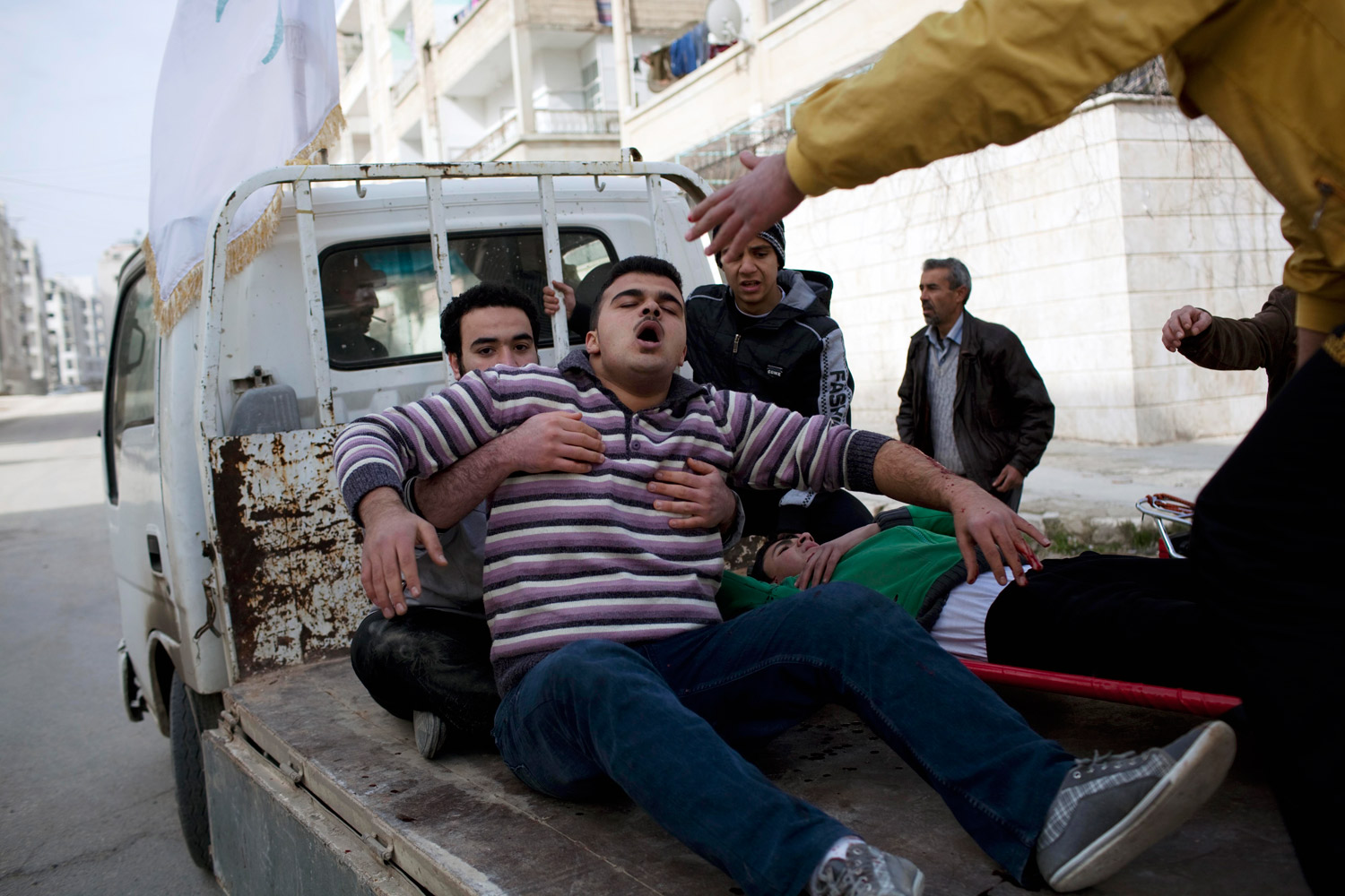 March 10, 2012. Injured men are carried to a hospital during fierce fighting between Free Syrian Army fighters and government troops in Idlib, Syria.