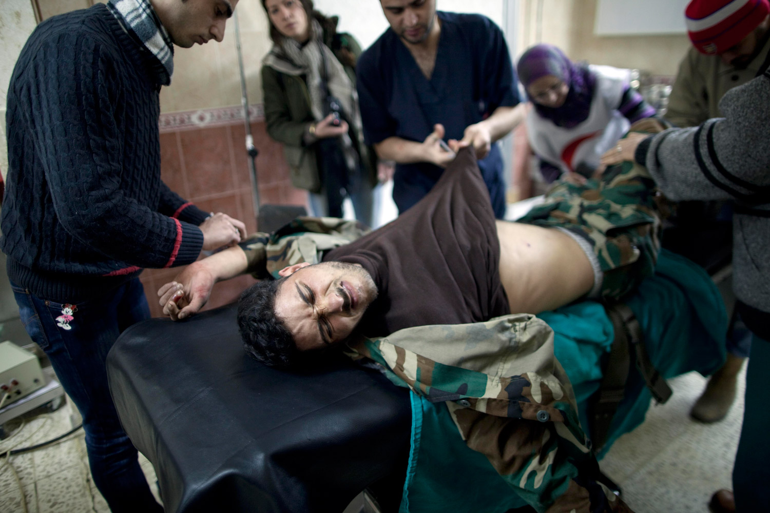 March 10, 2012. A Free Syrian Army fighter is treated by doctors after being injured during fighting against government troops in Idlib, Syria.