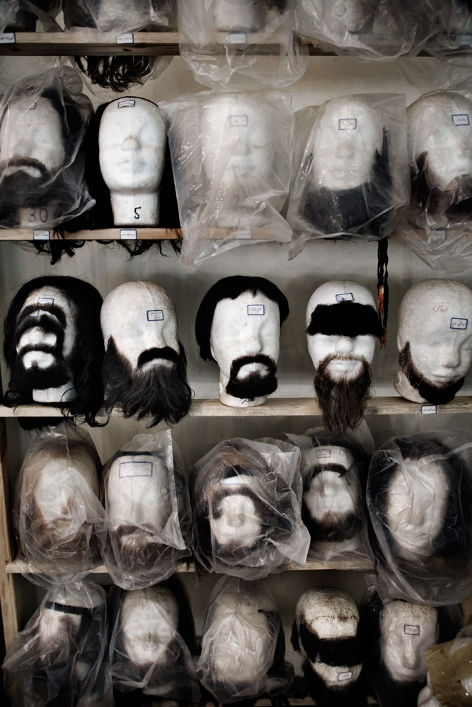 Fake wigs and moustaches rest on display heads inside the hair and makeup department on the set of Moktar in Abadan, Iran.