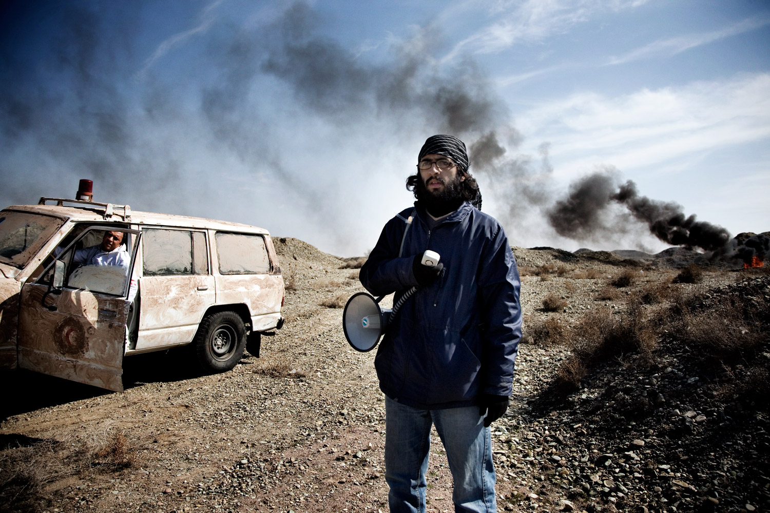 The assistant director prepares for a scene on the set of a war film in Tehran.