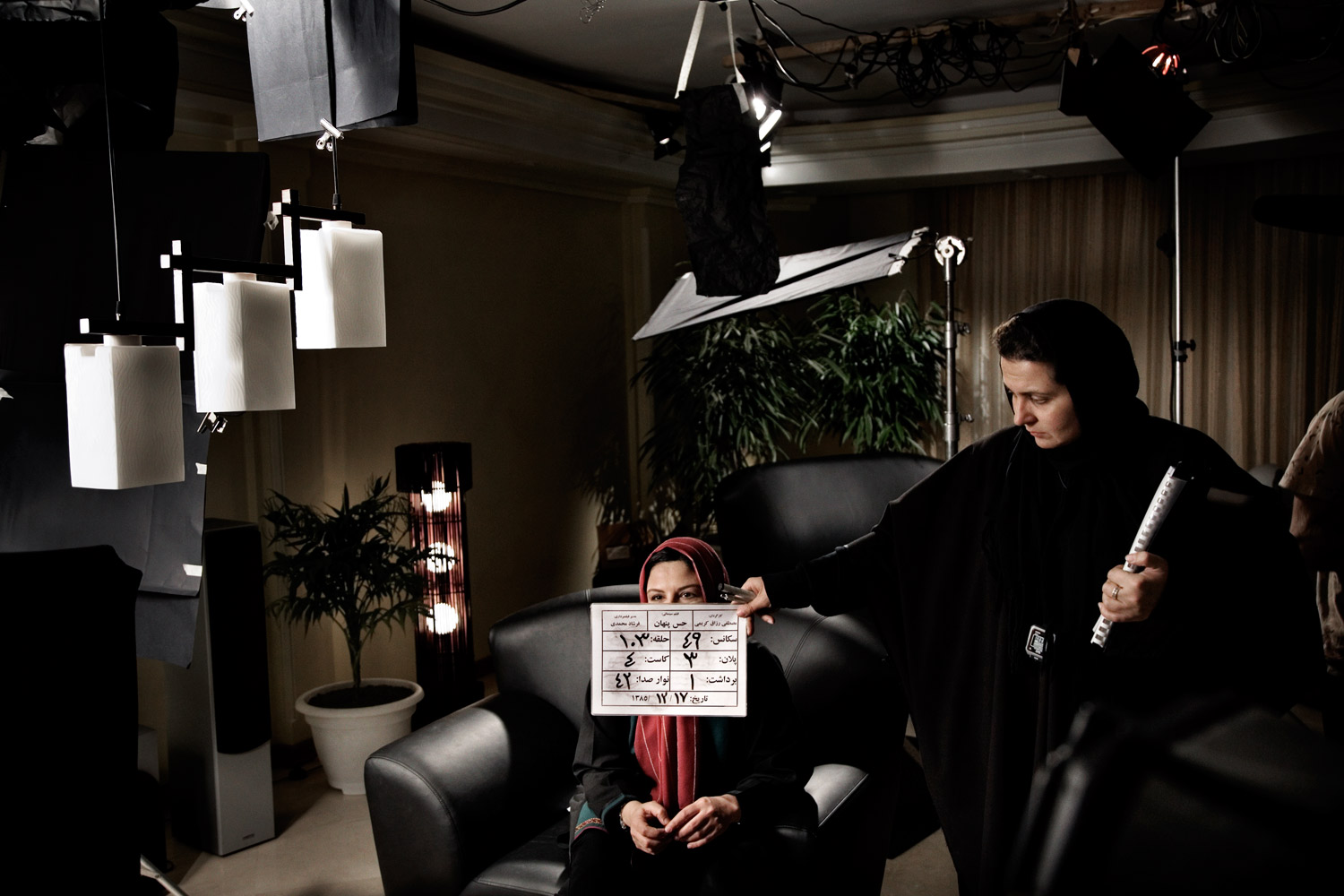 An actress and crew member prepare for a scene on the set of director Rusagh Karimi's film The Hidden Meaning in Tehran.