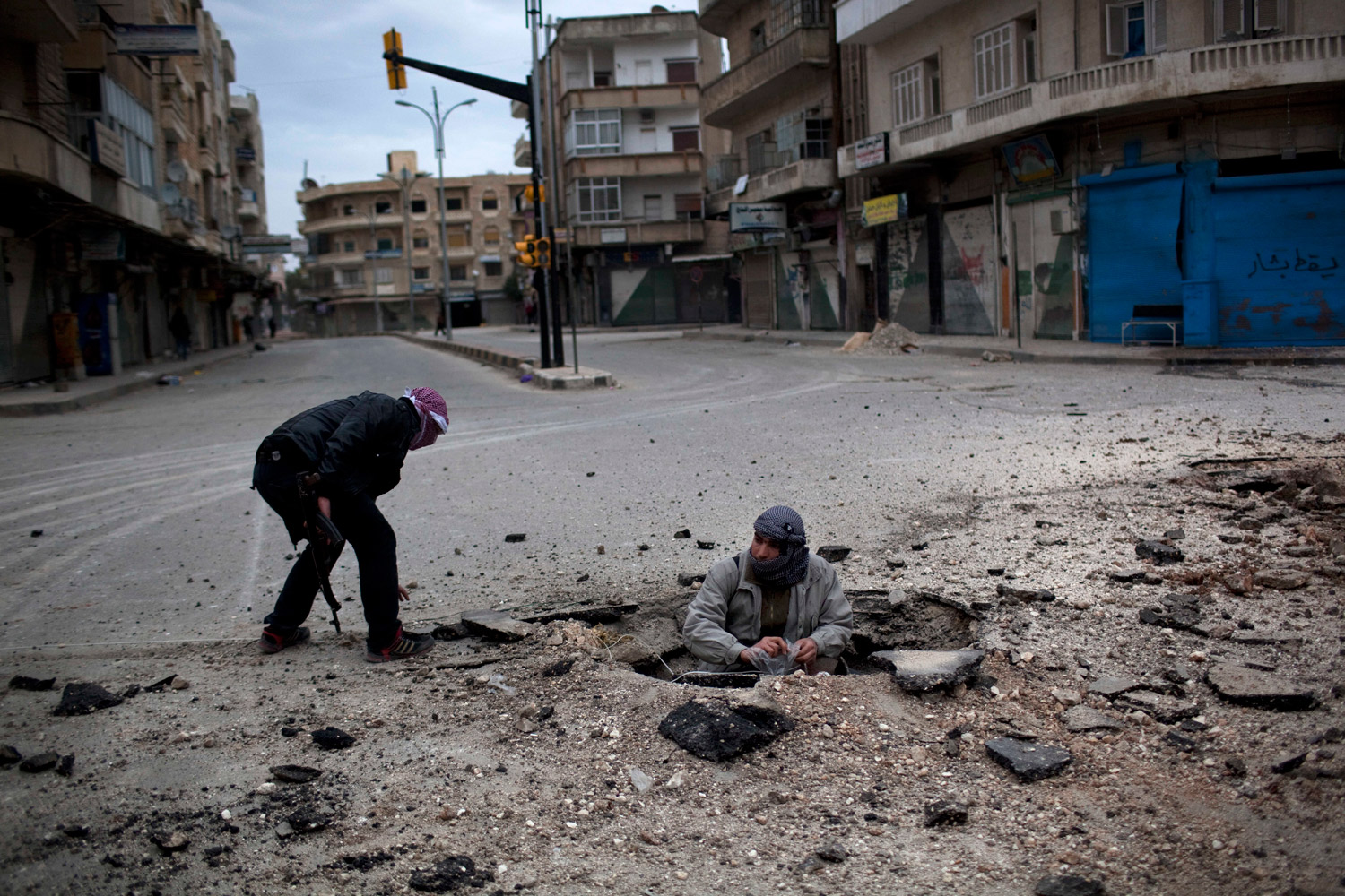 March 11, 2012. Syrian rebels plant a makeshift explosive device to destroy a Syrian Army tank during a day of heavy fighting with Syrian Army forces in Idlib. In the previous days, troops had encircled Idlib, and tank shells pounded the city from dawn until evening.