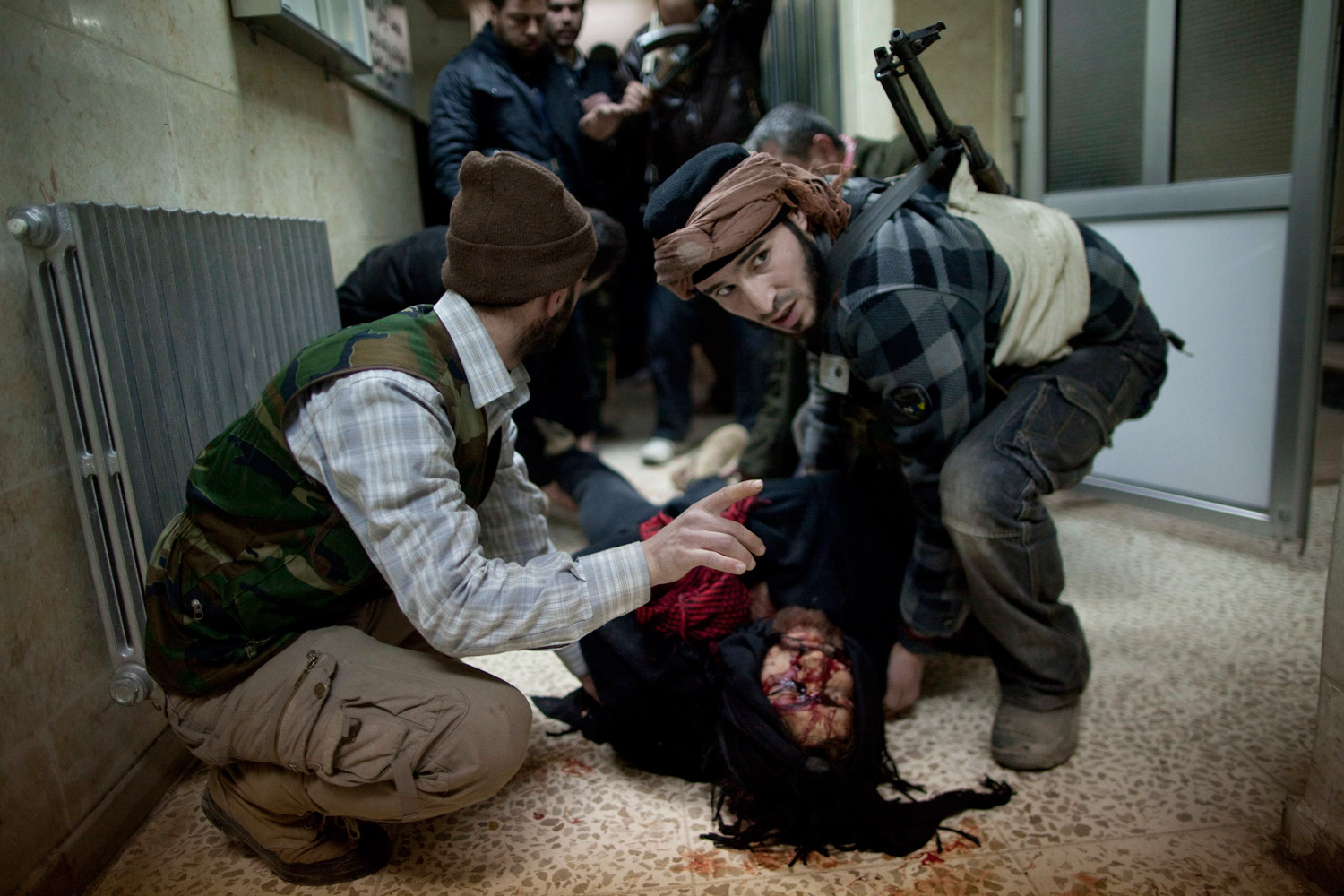 March 11, 2012. Syrian rebels carry the dead body of a comrade to a morgue after heavy fighting with Syrian government forces in Idlib, north Syria.