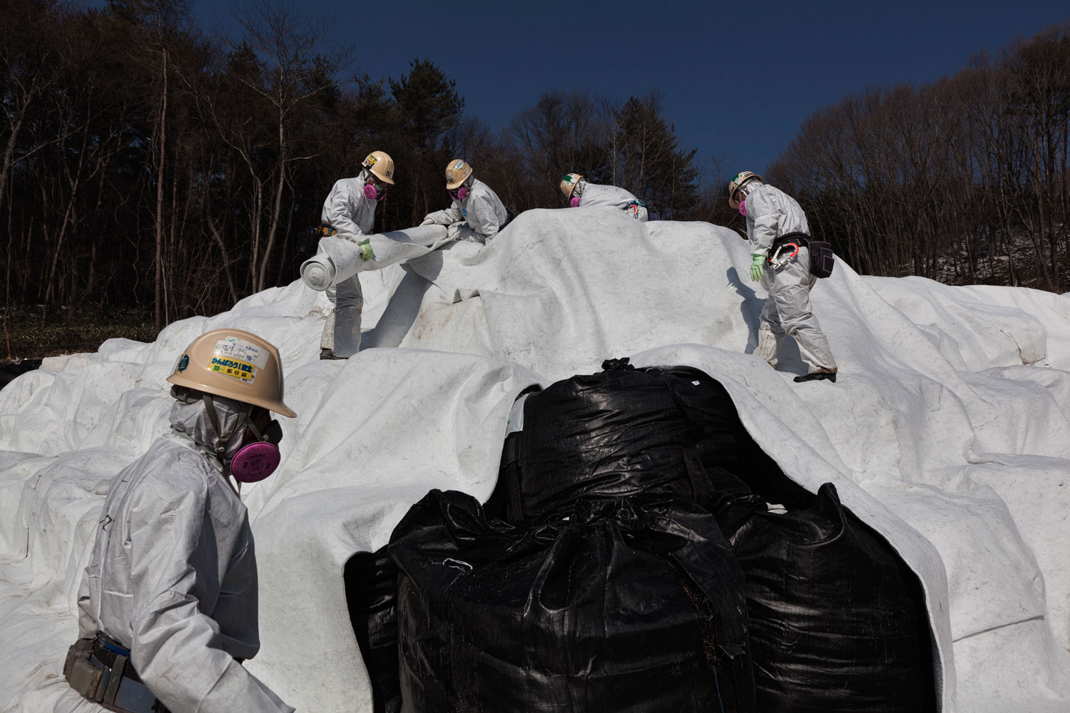 Feb. 24, 2012. Fukushima Prefecture, Japan. Workers cover bags of soil contaminated by radiation.