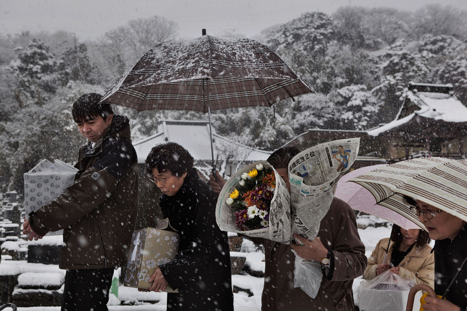 Feb. 25, 2012. Ishinomaki, Japan. A family buries the remains of family members lost almost a year before.