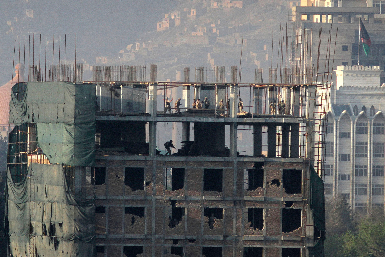 April 16, 2012. Afghan special forces are seen on top of a building that was occupied by militants in Kabul.