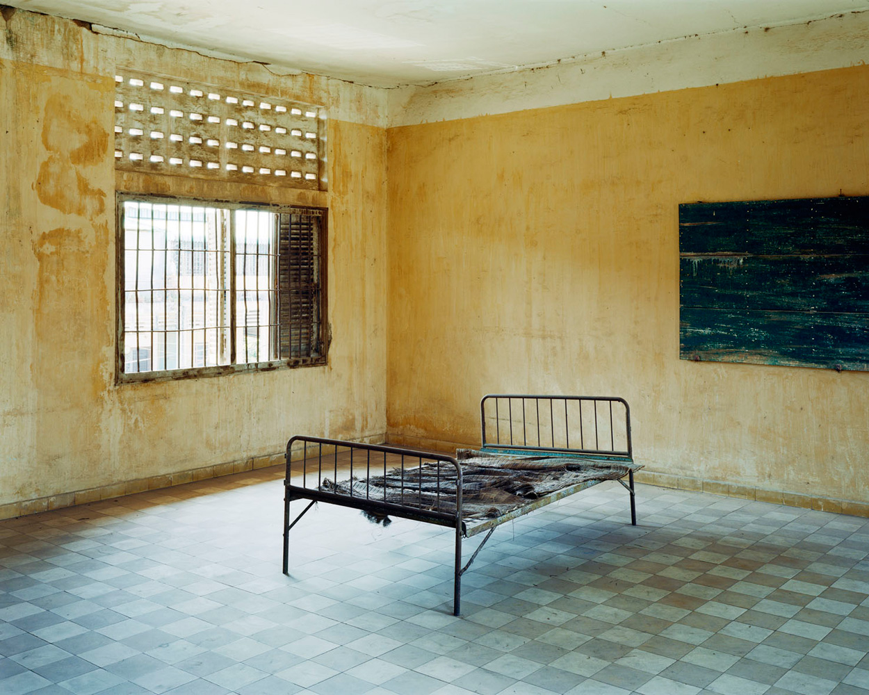 """Tuol Sleng Genocide Museum , Phnom Penh – Cambodia. 2010.Torture bed in Building  A  of a secret prison, which in 1977 and 1978 was converted into a set of rooms with windows that were paneled with glass to minimize the sound of prisoners' screams heard outside the facility in times of torture. Building """"A"""" was used for detaining cadres who were accused of leading the uprising against the Pol Pot revolution. On Jan. 7, 1979, the government collected all the evidence in the prison such as photographs, films, prisoner confession archives, torture tools, shackles and victims' corpses. Now the evidence of the criminal regime is on display for visitors."""