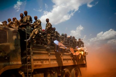A truck filled with soldiers of the Sudan People's Liberation Army (SPLA), the military force of South Sudan, rushes toward the front line in mid-April.