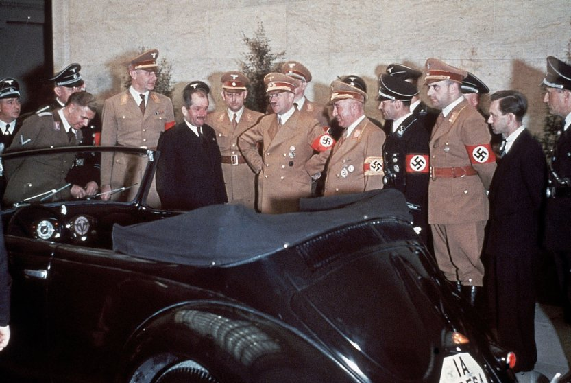 The automobile engineer Ferdinand Porsche (in suit), Adolf Hitler and, immediately to Hitler's left, the head of the German Labour Front, Robert Ley, admire Hitler's birthday gift on his 50th birthday: a convertible Volkswagen.