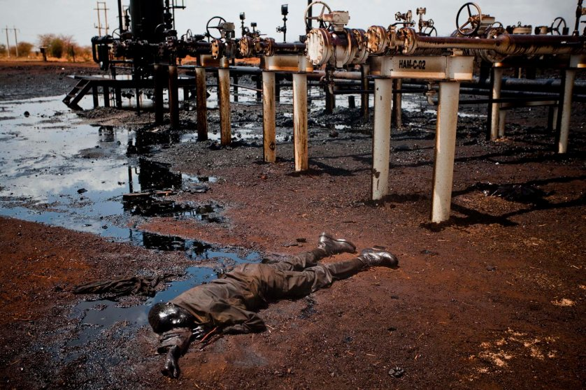 A soldier of the northern regime's army, the Sudan Armed Forces (SAF), lies dead, immersed in oil next to a leaking petroleum facility after heavy fighting with southern SPLA troops after they entered Heglig in mid April.